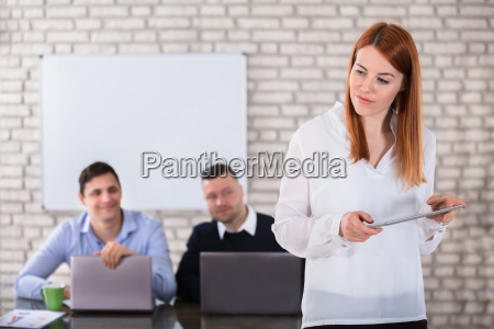 businessmen looking at woman holding digital