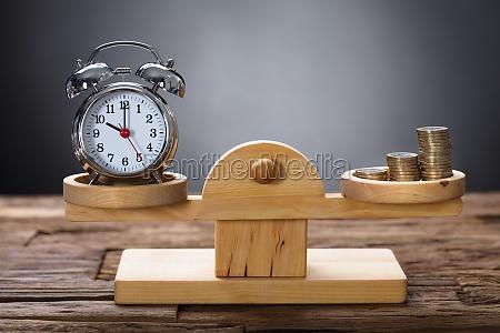 clock and coins balancing auf hoelzernen