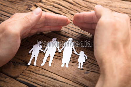 businessman covering paper family at wooden
