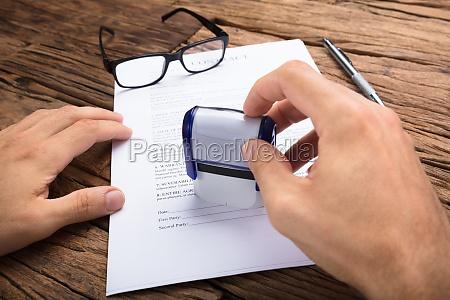 geschaeftsmann stempelt vertrag papier bei tisch