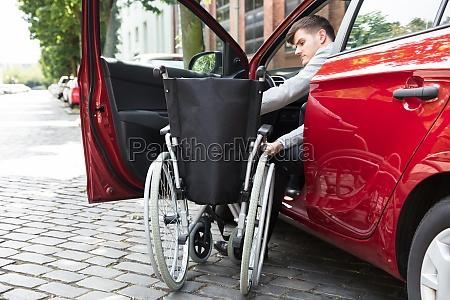 mann sitzt im auto klappt seinen