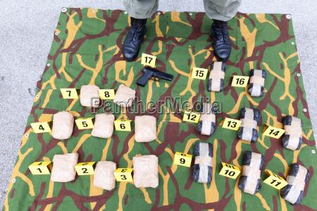 polizeibeamte der vor uebergreifenden drogenpaketen steht
