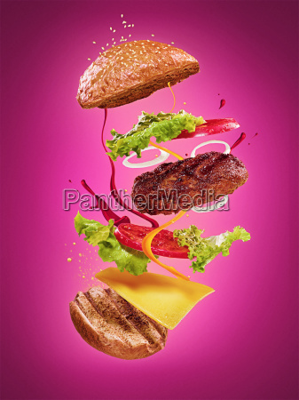 the hamburger with flying ingredients on