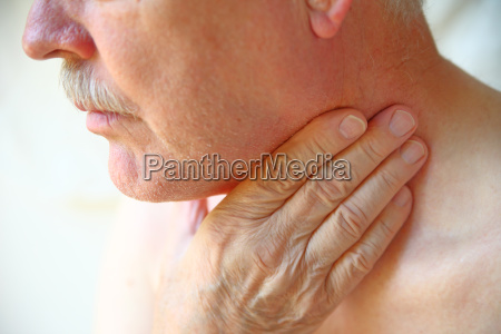 senior man has hand on throat