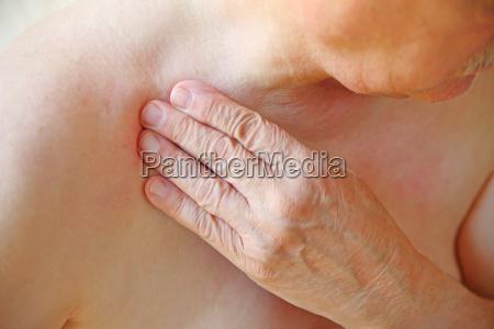 senior touches his aching shoulder closeup