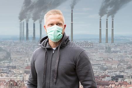 mann traegt mundmaske gegen luftverschmutzung