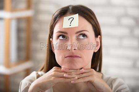 die stirn der geschaeftsfrau mit fragezeichen