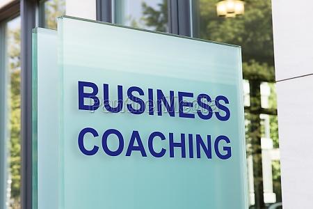 business coaching schild auf glastafel vor