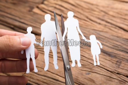hand cutting paper family over wooden