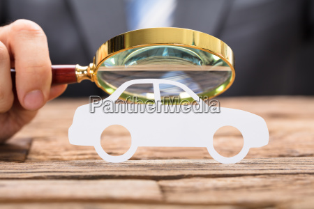businessmans hand examining paper car with