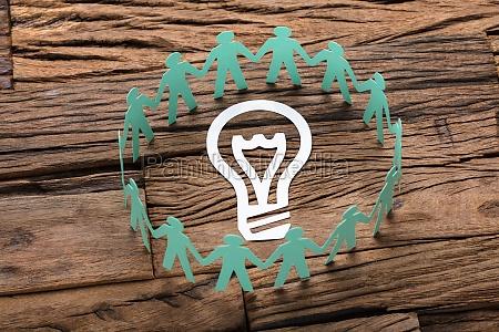 green paper business team surrounding light