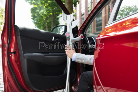 disabled person standing near car