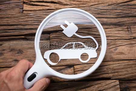 businessmans hand holding magnifying glass over