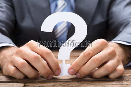 businessman holding paper question mark at
