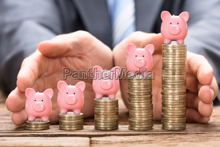 businessman protecting piggybank on stacked coins