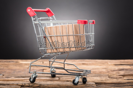 package in shopping cart on wooden