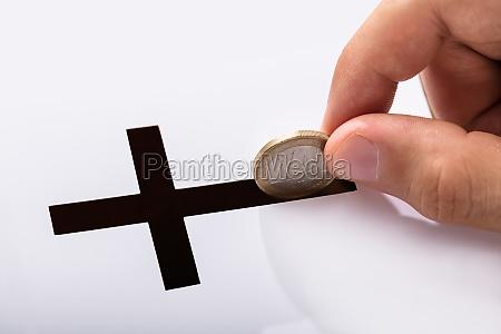 hand die muenze in kruzifix schlitz