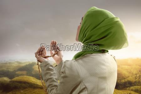 junge moslemische frau die gebetsperlen haelt