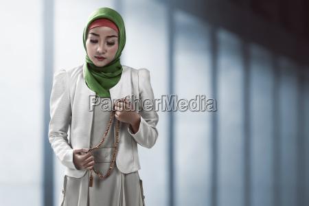 muslimische frau haelt gebetskette