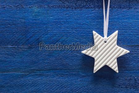 weihnachtskarte mit stern auf blauem holz