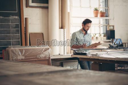 entrepreneur in his workshop checking figures