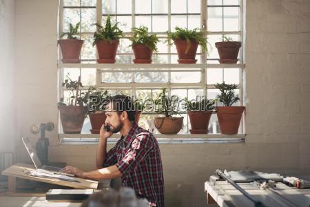 designer entrepreneur using his phone while
