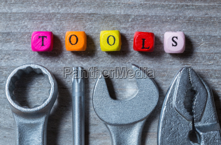 tools buchstabenwuerfel und werkzeug auf grauem
