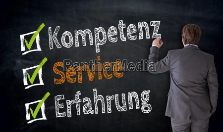 businessman schreibt kompetenz service erfahrung auf