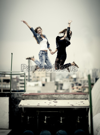 two young women jumping on a