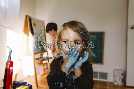 young girl holding her hands covered