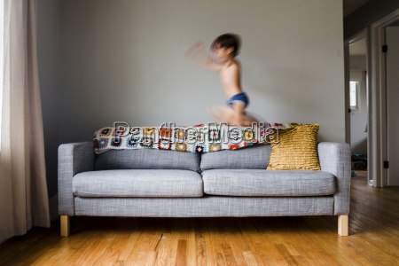 boy child jumping on a sofa