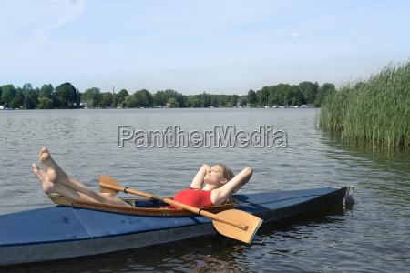 woman sunbathing in a kayak on