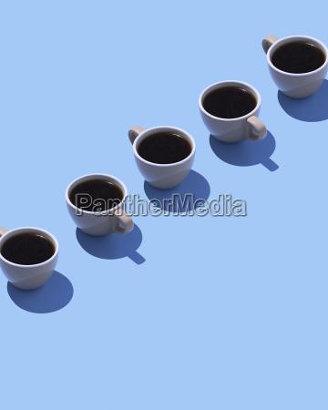 five coffee cups on light blue