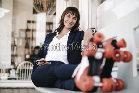 businesswomanwearingrollerskates2choldingsmartphone