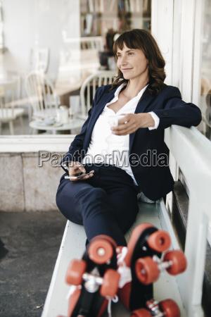 businesswomanwearingrollerskates2cdrinkingcoffeeandusingsmartphone