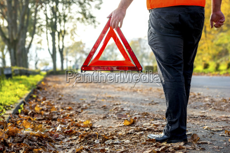 legs of man with warning triangle