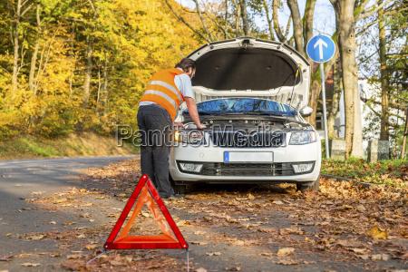 man examining damaged car at roadside