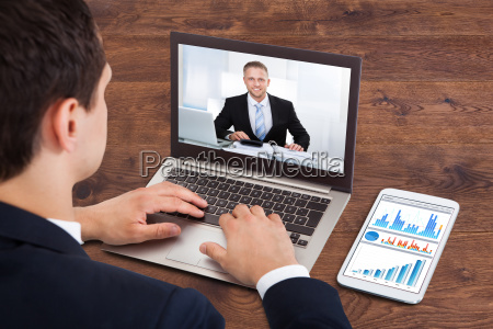 businessperson video conferencing with male colleague
