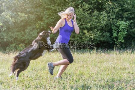 junge blonde frau laeuft mit hund