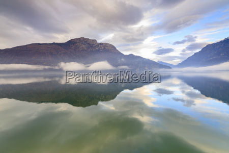 mountains reflected in lake mezzola at