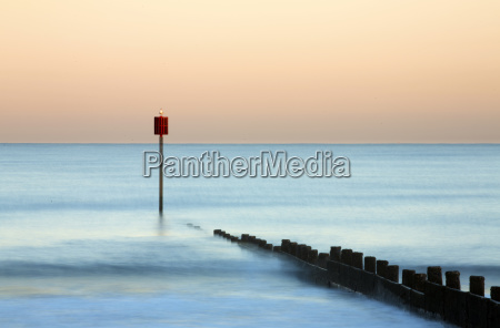 groyne and post at sunset on