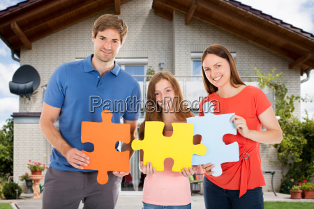 happy family holding colorful jigsaw puzzles