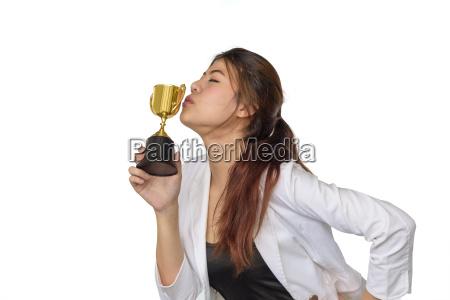 beautiful asian business woman kiss trophy