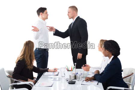boss blaming male executive in meeting