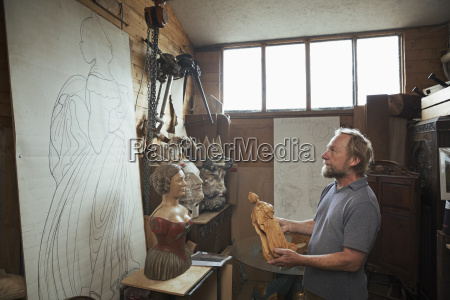 a craftsman wood carver holding a