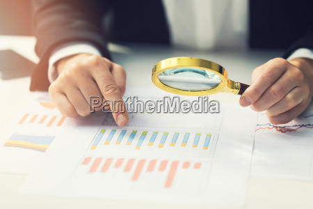 business women using magnifying glass to