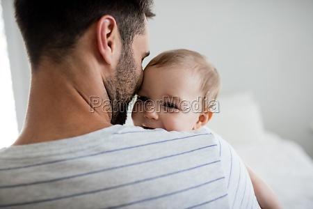 vater der sein baby haelt