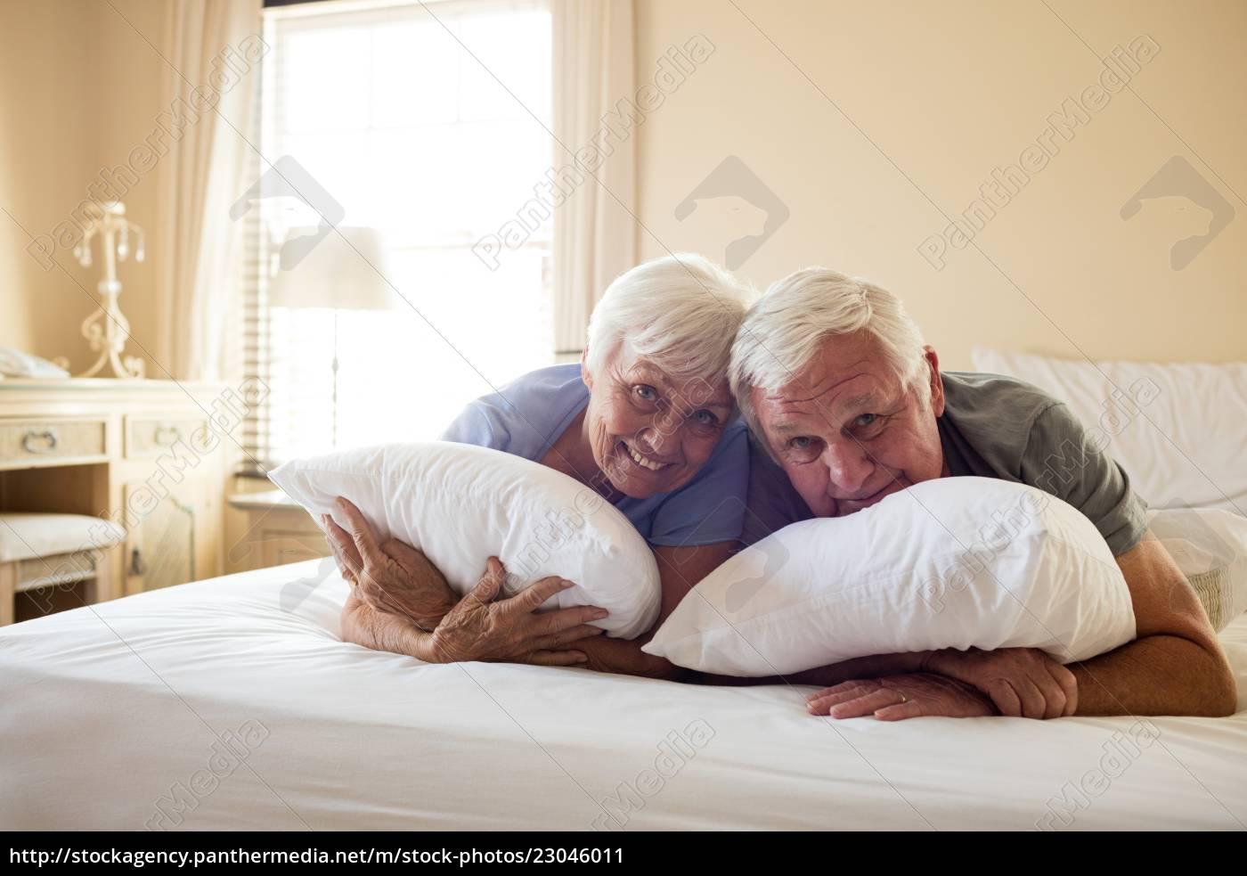 Gluckliche Altere Paare Die Auf Bett Liegen Lizenzfreies Bild