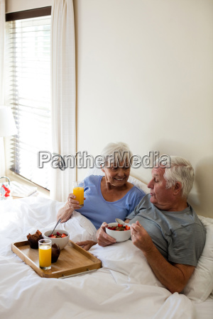 senior couple having breakfast on bed