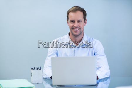 portrait of smiling dentist working on